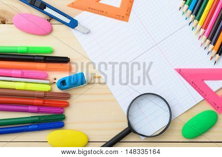 School stationery with pages from notebook copyspace on wooden board