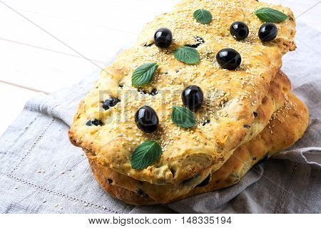 Stack of traditional Italian bread focaccia with olive garlic and herbs. Homemade traditional Italian bread focaccia.