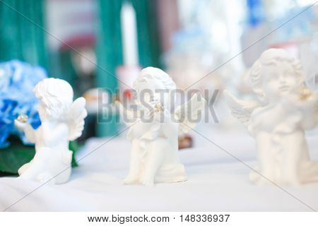 Three statues of angels on the table