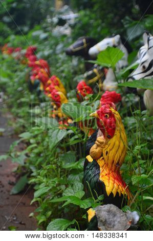 puppets, green, horses, red, sculptures, trees, yellow, chicken, grass, black, fake, background