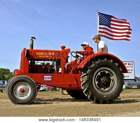 ROLLAG, MINNESOTA, Sept 1. 2016: Two unidentified men operate an old restored Farmers Union Co-op No. 3 tractor in a parade at the West Central Steam Threshers Reunion in Rollag, MN attended by 1000's held annually on Labor Day weekend.