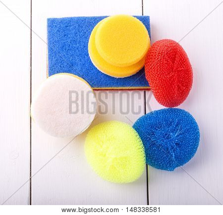 New yellow red and blur sponge for washing dishes on a white background shot from above