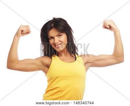 Cheerfully smiling  sporty woman demonstrating biceps, isolated on white background