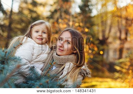 Family walk. Mother hugs daughter. Autumn Park. Cute family relationships.