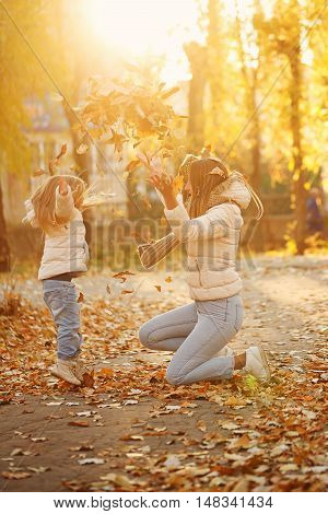 Family walk. Mother and daughter throw up fallen leaves. Autumn Park. Cute family relationships.