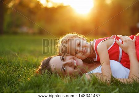 Mother and daughter lying on the lawn. Family in the city park outdoors. Happiness of motherhood and childhood.