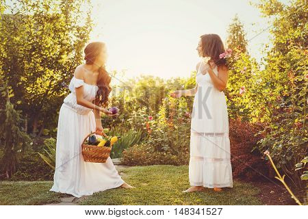 Two cute sisters in long white dresses and a basket with harvest. Girl shows her sister harvest. Ripe fruits and vegetables. Rich harvest. Agriculture.