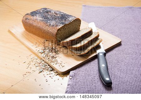 Freshly baked sliced banting seed loaf or paleo bread on a board with bread knife and seeds