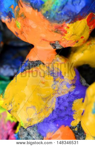 rocks covered with colorful paint close-up. Stones in the paint with streaks. Abstract background