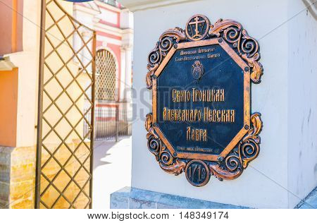 SAINT PETERSBURG RUSSIA - APRIL 25 2015: The old signboard at the entrance to St Alexander Nevsky Lavra with the Cyrillic script on April 25 in Saint Petersburg.