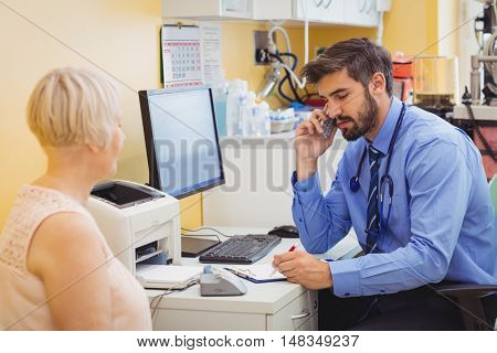 Doctor sitting at his desk and talking on phone at the hospital