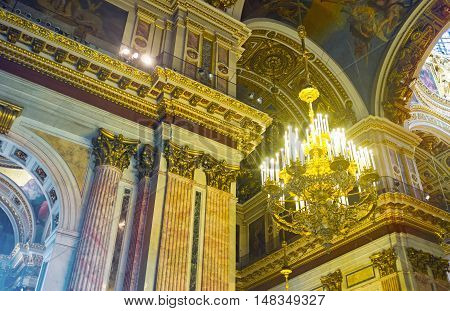 SAINT PETERSBURG RUSSIA - APRIL 25 2015: The massive chandelier and richly decorated walls of St Isaac's Cathedral with stone painted carved and gilt elements on April 25 in Saint Petersburg.