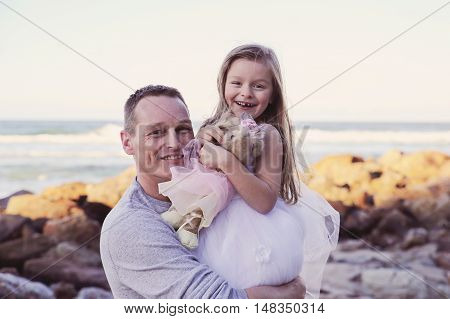 Father holding daughter on the beach toning