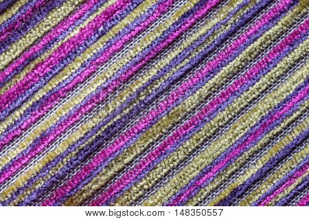 Purple multicolor background of a knitted textile material with diagonal pattern. Fabric with a striped texture closeup.