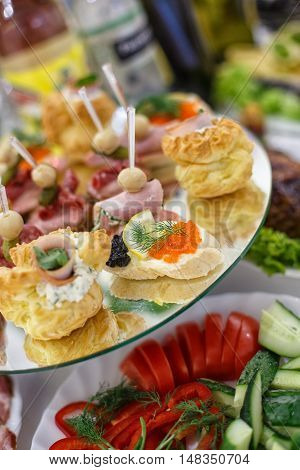 Beautifully decorated catering banquet table with different food snacks and appetizers with sandwich, caviar, on corporate birthday party event or wedding celebration