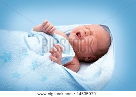 One week old crying baby in a blanket on blue background