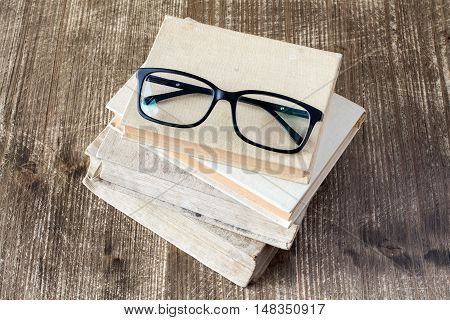 Top view of books and reading glasses on the wooden background.