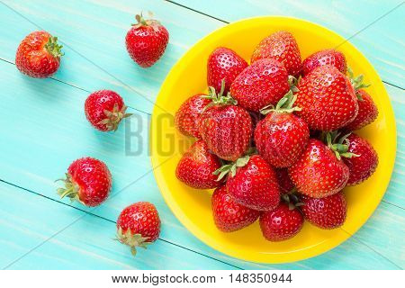 Yellow plate with red strawberries on blue wooden background