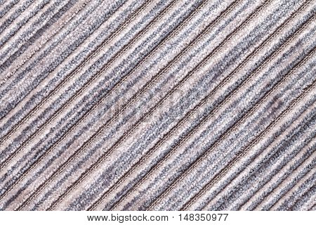 Gray background of a knitted textile material with diagonal pattern. Fabric with a striped texture closeup.