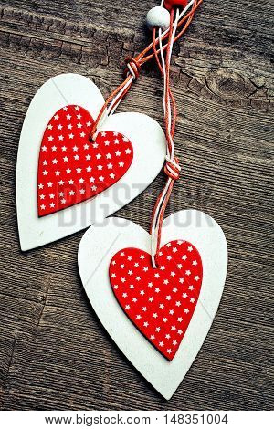 two decorative red and white heart on a wooden background. background for Valentine