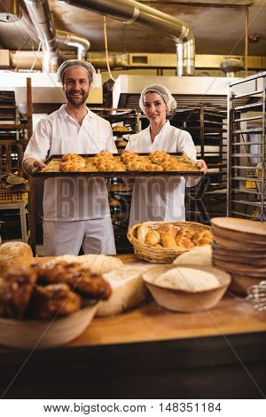 Portrait of female and male baker holding a tray of michetta in bakery shop