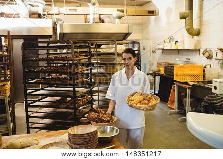 Female baker holding basket of sweet foods at bakery shop