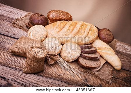 Fresh bread, baked goods, harvest on the farm, great food, ears of wheat, burlap sack of grain, a table of old wood, close-up bread, spilling wheat