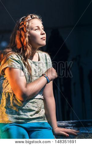 Portrait of a beautiful young teenage girl sitting on window of the old abandoned house