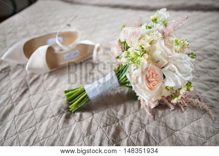 Bridal accessories: beige shoes and bride's bouquet on a bed with pink background