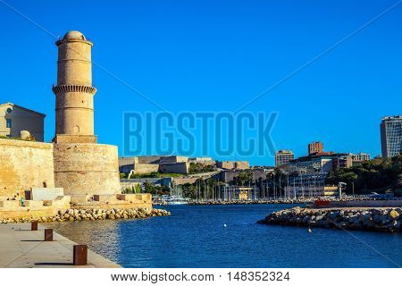 Most watchtower is reflected in the blue water port. Fort St. John in Marseille
