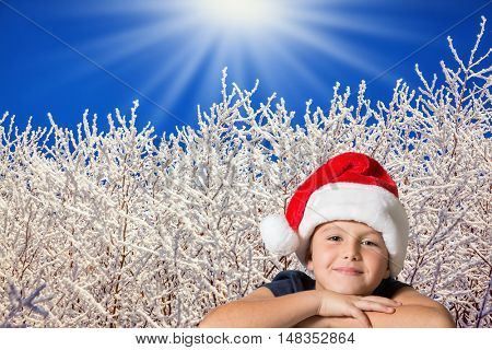 Beautiful seven year old boy in red hat of Santa-Claus smiling  on the background of the winter forest