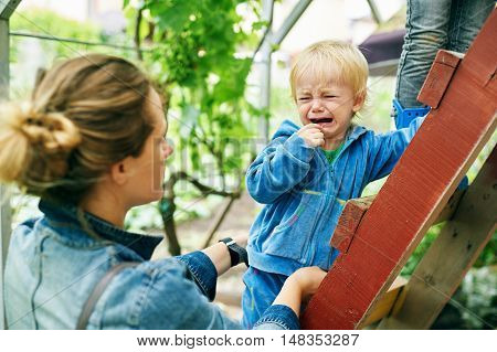 Little boy crying looking at the mother standing on the stairs
