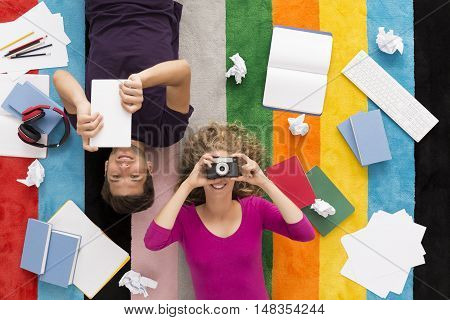 Top view of a student reading notes and his girlfriend holding a camera colorful background