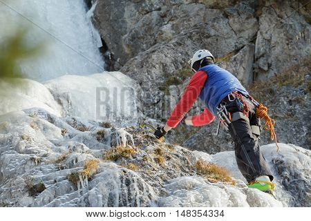 Active ice climbing mountaineer on winter natural rocks outdoor