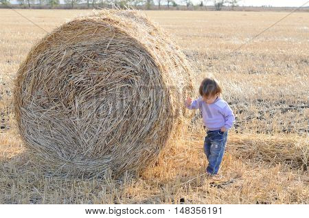 Little kid near sheaf of hay in the autumn field