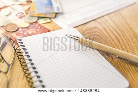 Blank notepad with pen and financial elements - Conceptual image for planing and organizing the financials with a graph notepad pen eyeglasses and money cards and bills in the background.