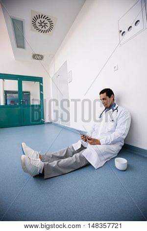 Doctor sitting on floor and using digital tablet in hospital corridor
