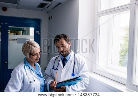 Doctors discussing over clipboard in hospital