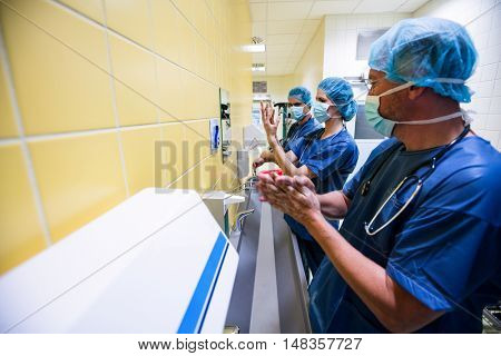 Group of surgeons washing their hands in hospital
