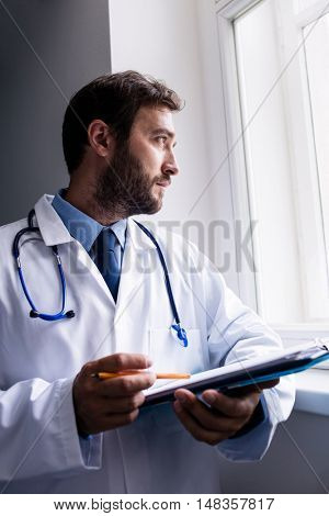 Thoughtful doctor looking through window while holding clipboard in hospital