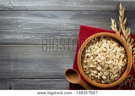 bowl of oat flakes at wooden background