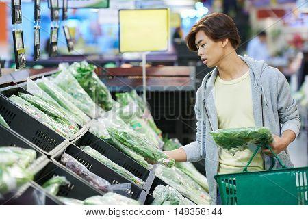 Vietnamese vegetarian choosing greens for smoothie in supermarket