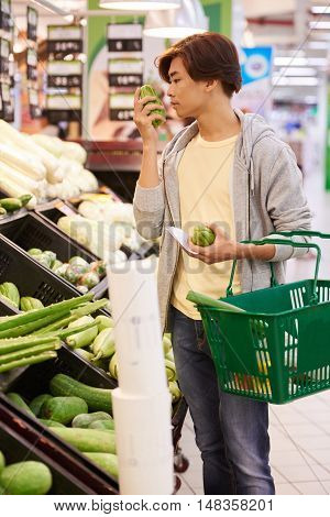 Young man smelling vegetables before buying them