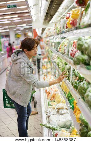 Vegetarian guy choosing ingredients for salad in supermarket