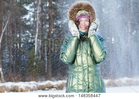 Laughing young woman is holding hands in woolly mittens near face during snowstorm in winter forest outdoors