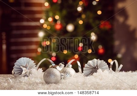 Composite image of Christmas baubles against Christmas tree background