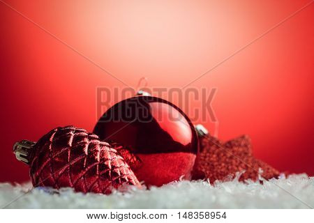 Composite image of Christmas bauble and pine cone against Christmas red background