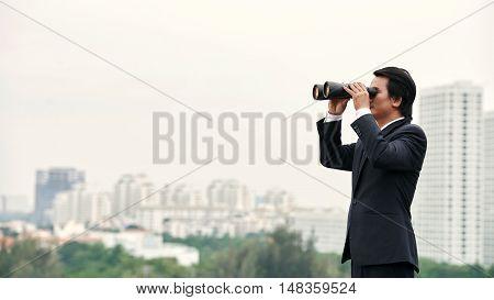 Asian businessman with binoculars enjoying city view