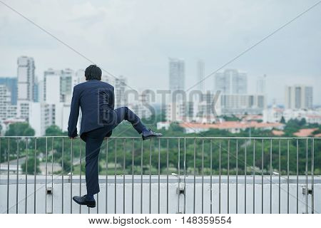 Businessman climbing over barrier on rooftop, rear view