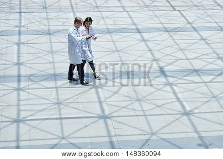 Asian doctors walking and discussing medical issues